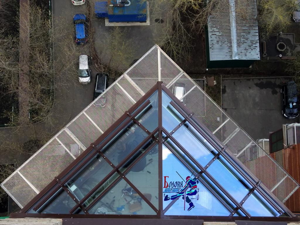Защитно-улавливающая решетка из нержавеющей стали под застекленной кровлей балкона